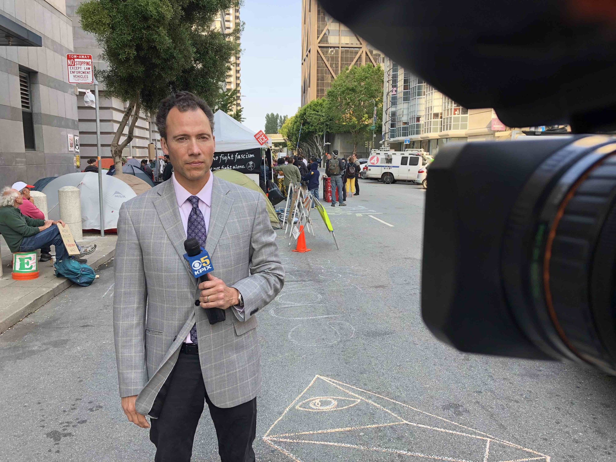 Live shot with protest in the background.