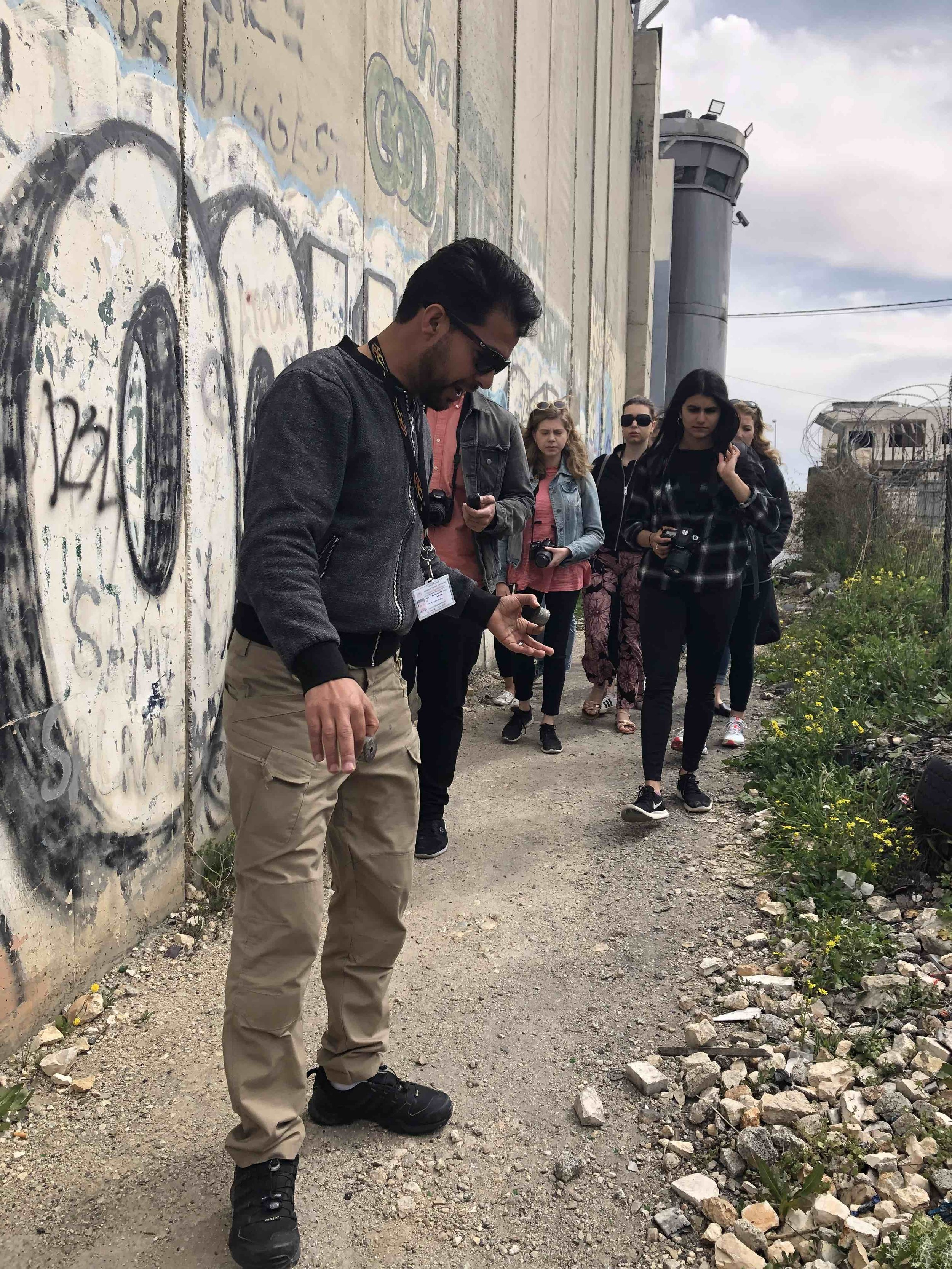 Tour guide Mustafa al Araj shows students the Palestinian side of the wall. He picked up several spent tear gas canisters.