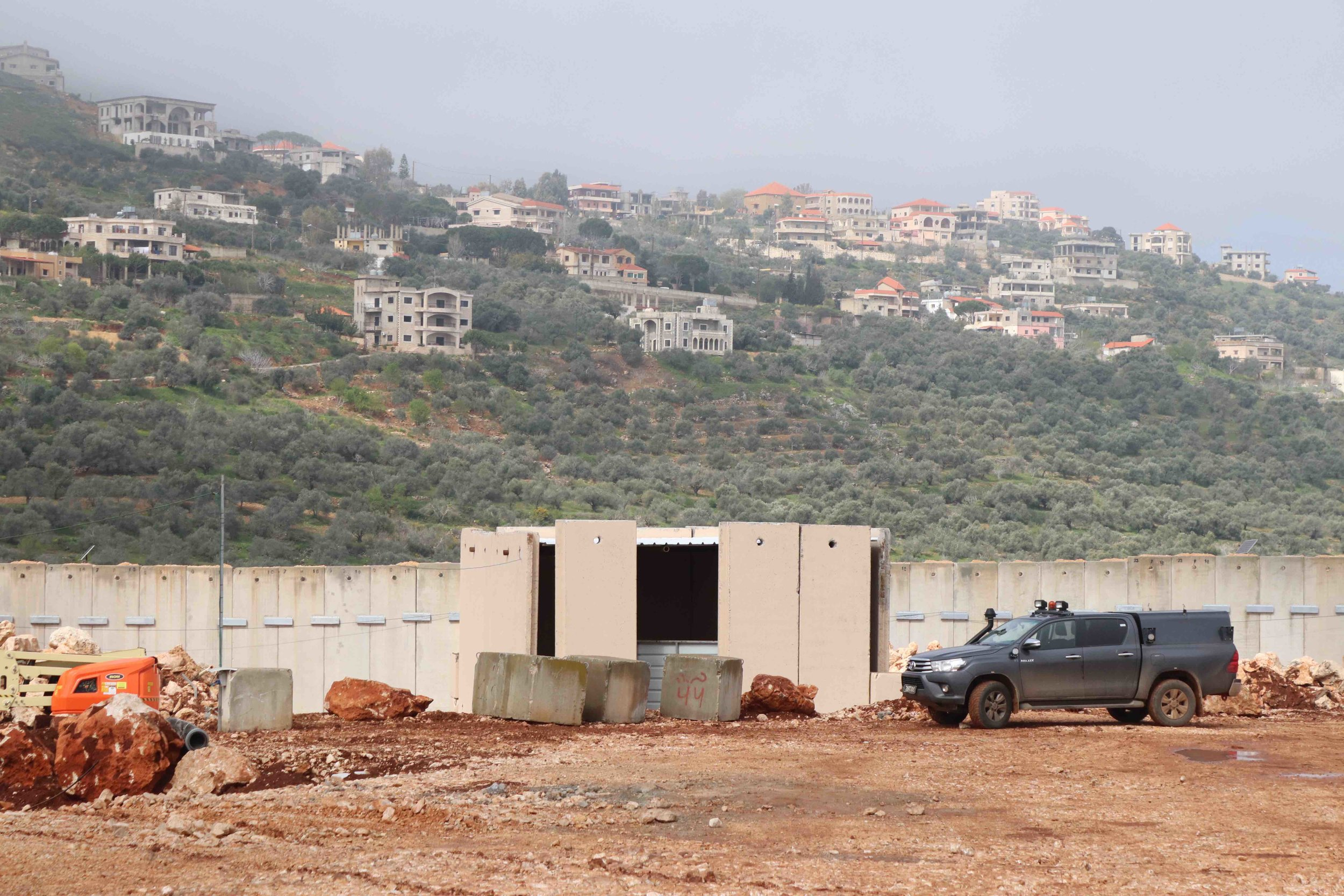 View over border wall from Metula to Lebanon. Israeli crews work to fill a tunnel.