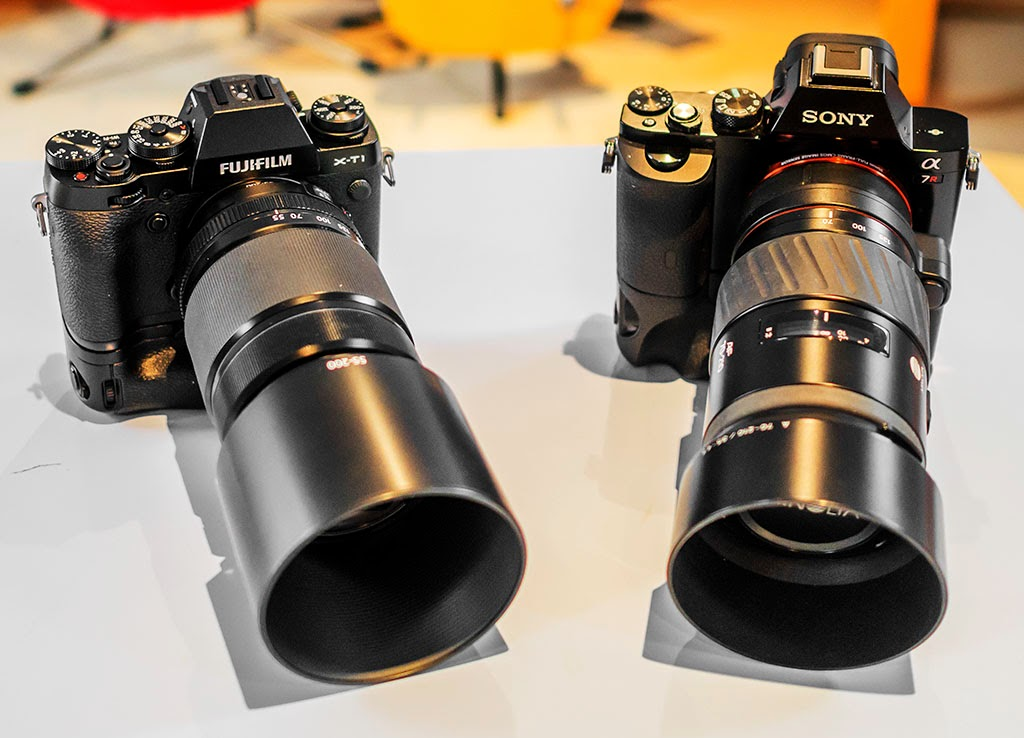 Fuji X-T1 + battery grip and 55-200mm lens compared in size to Sony A7r + nattery grip with 75-200 Minolta zoom.