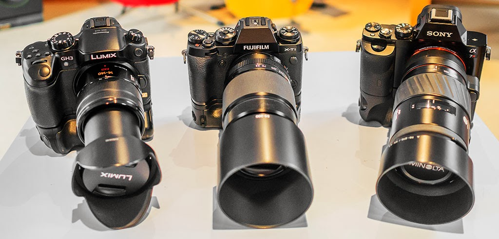 Fuji X-T1, Panasonic GH3, Sony A7r with battery grips and zoom lenses.