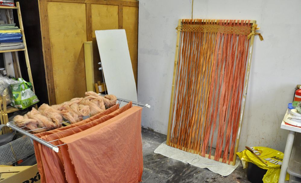 Starting the weaving. There is avocado-dyed wool and fabric drying on the left.