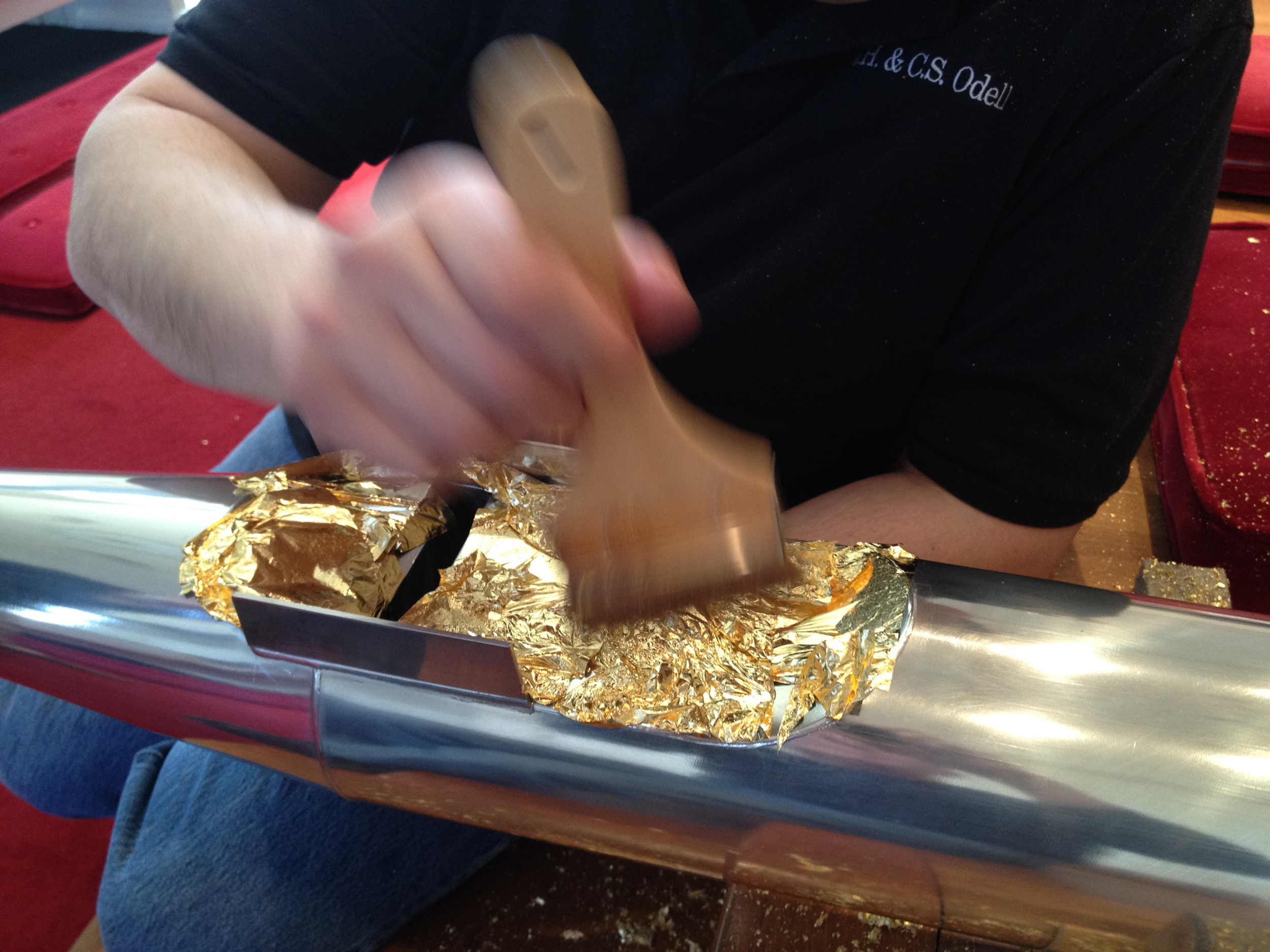 Applying 24 carat gold leaf to one of the facade pipes.