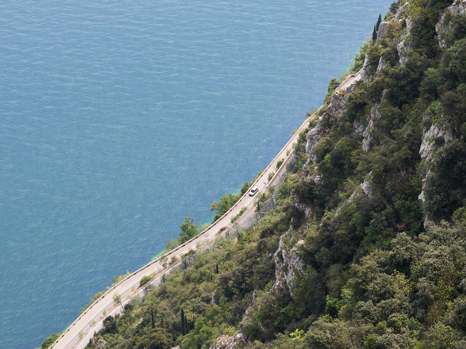 Areil view of a car driving alongside Lake Garda, Italy. Kirsty Owen Photography.