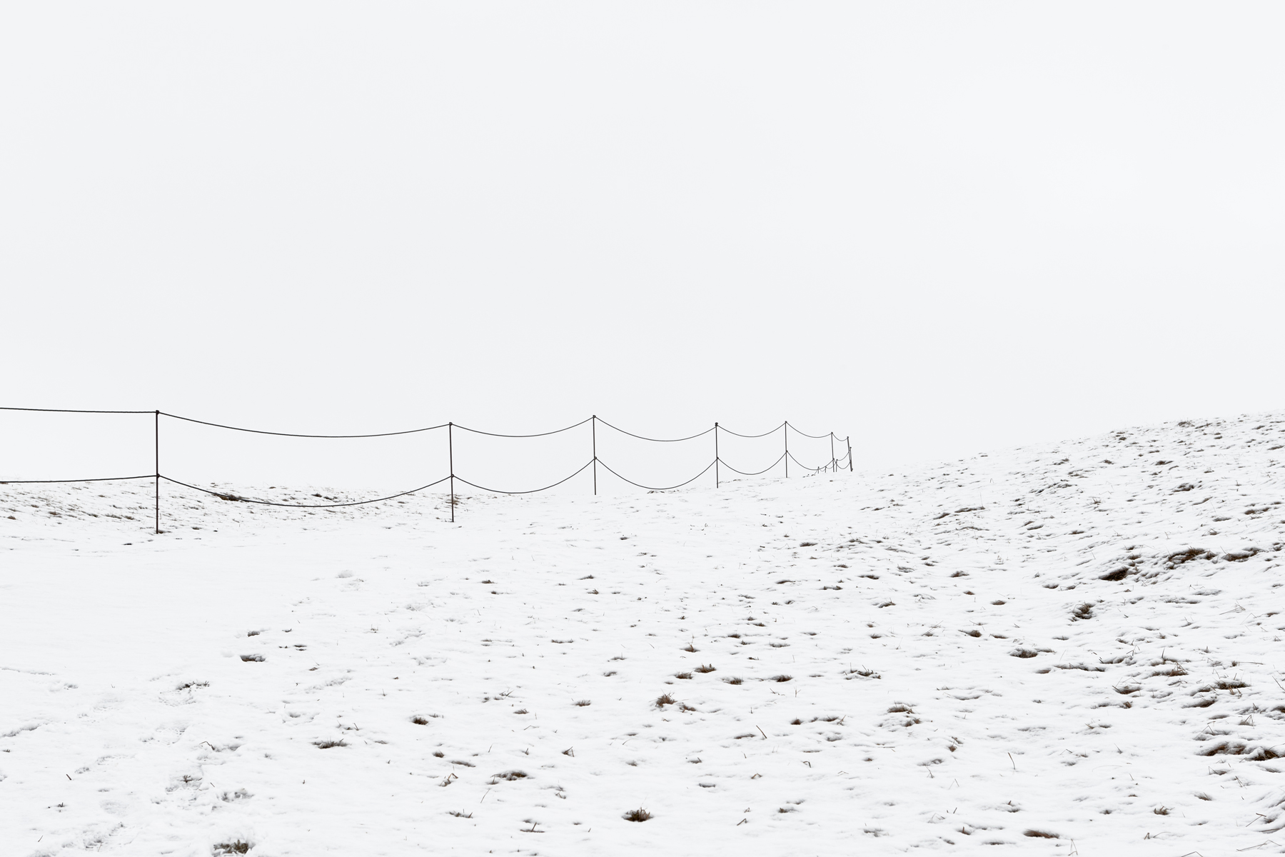 Snowy landscape in Iceland with small fence. Kirsty Owen Photography.