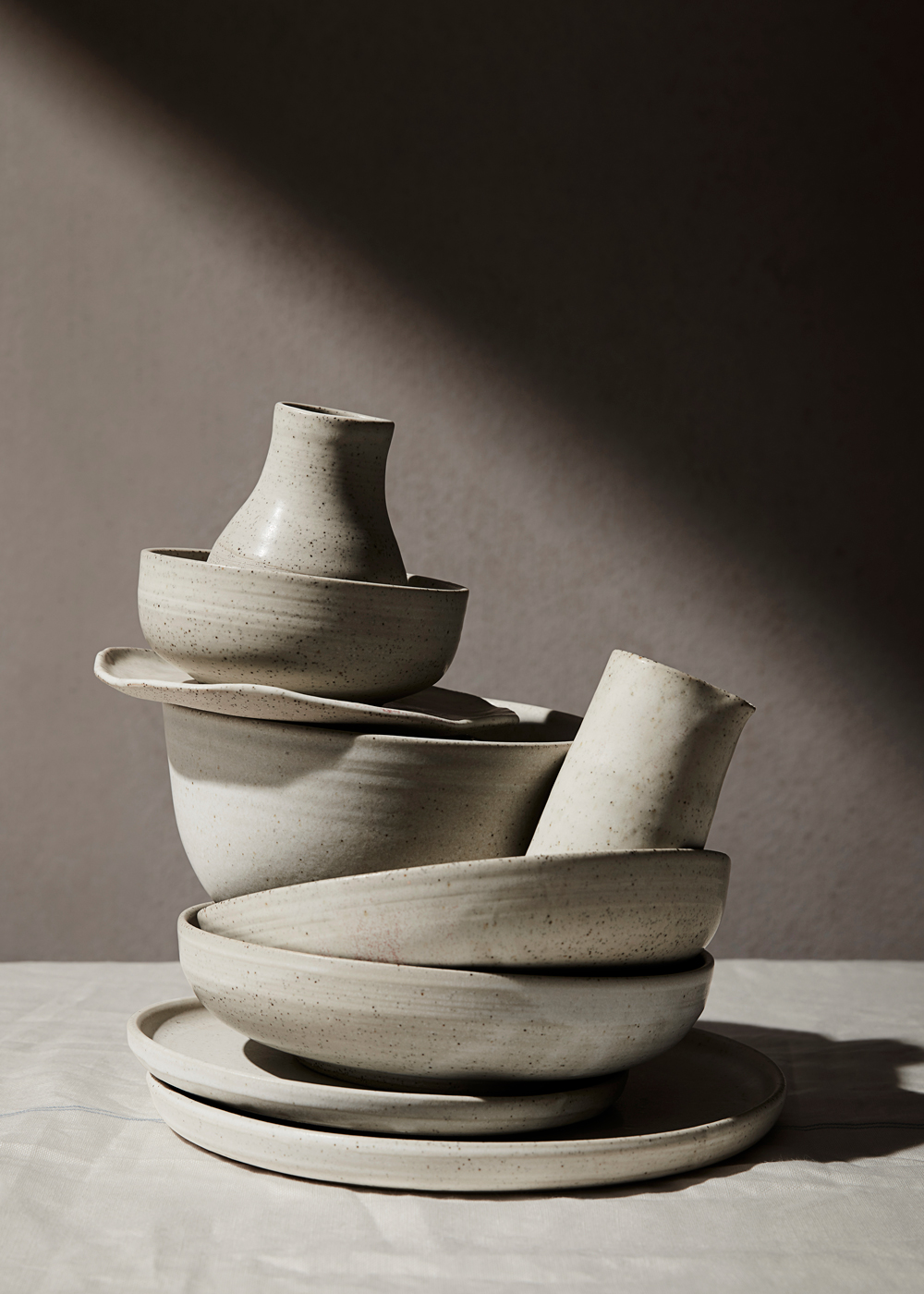 stacked pottery on linen kirsty owen lifestyle photography
