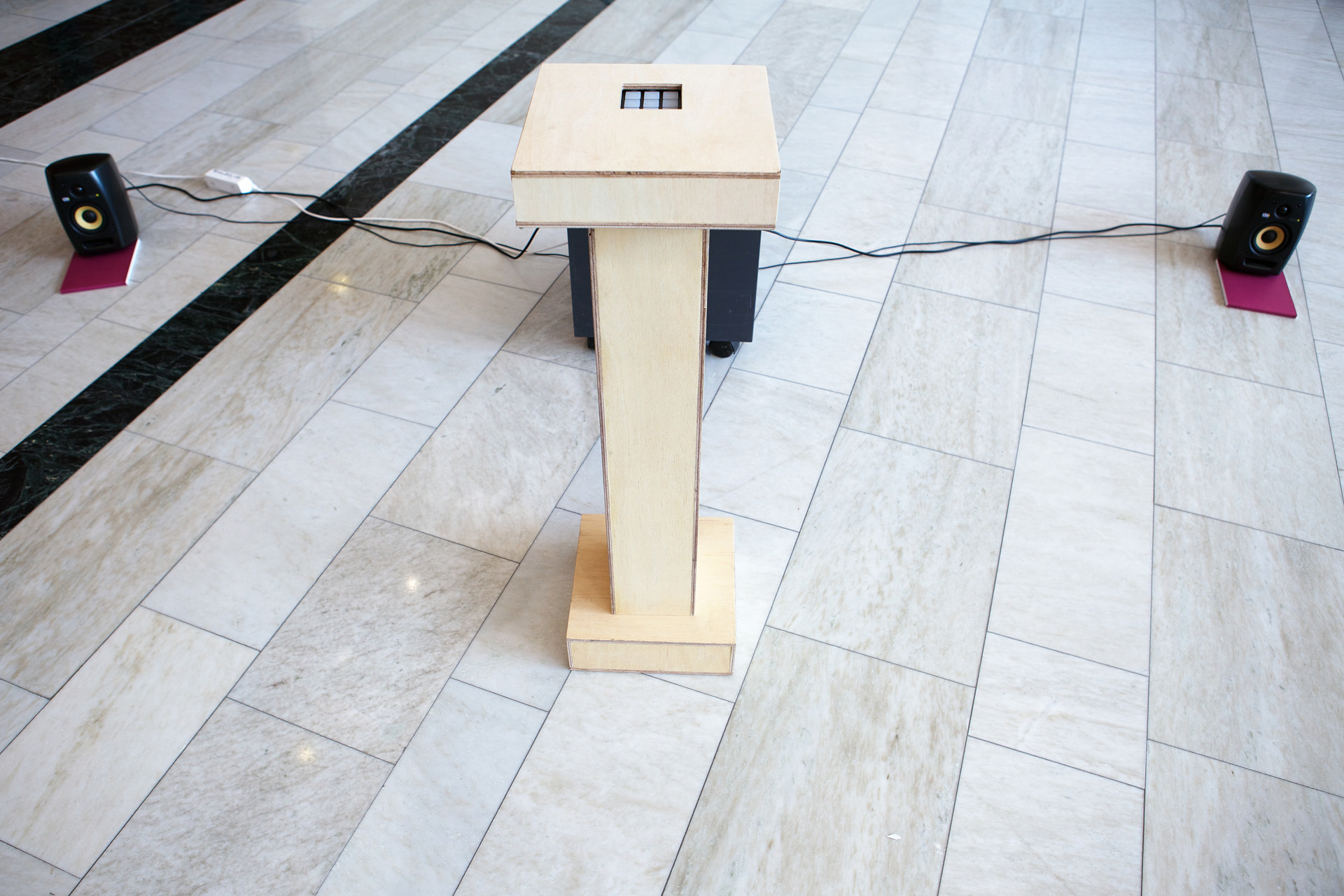 A wooden pedestal with nine buttons for the audience to jam with the gridded video clips.