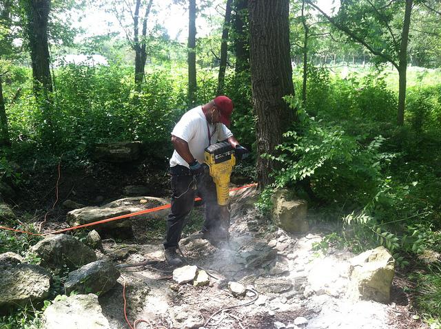 Tomaz Williams breaking apart the concrete liner of the original pond(photo by Sara Black)