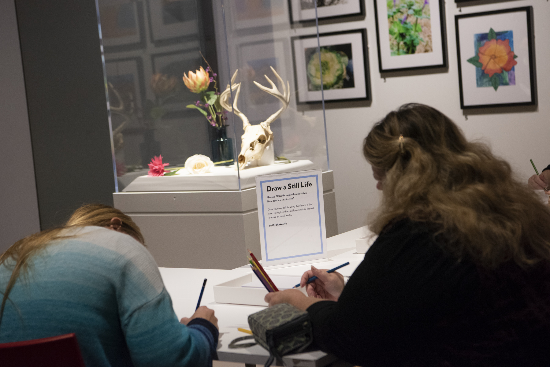 Exhibition visitors create their own art in a drawing studio at the end of a Georgia O'Keeffe exhibition.