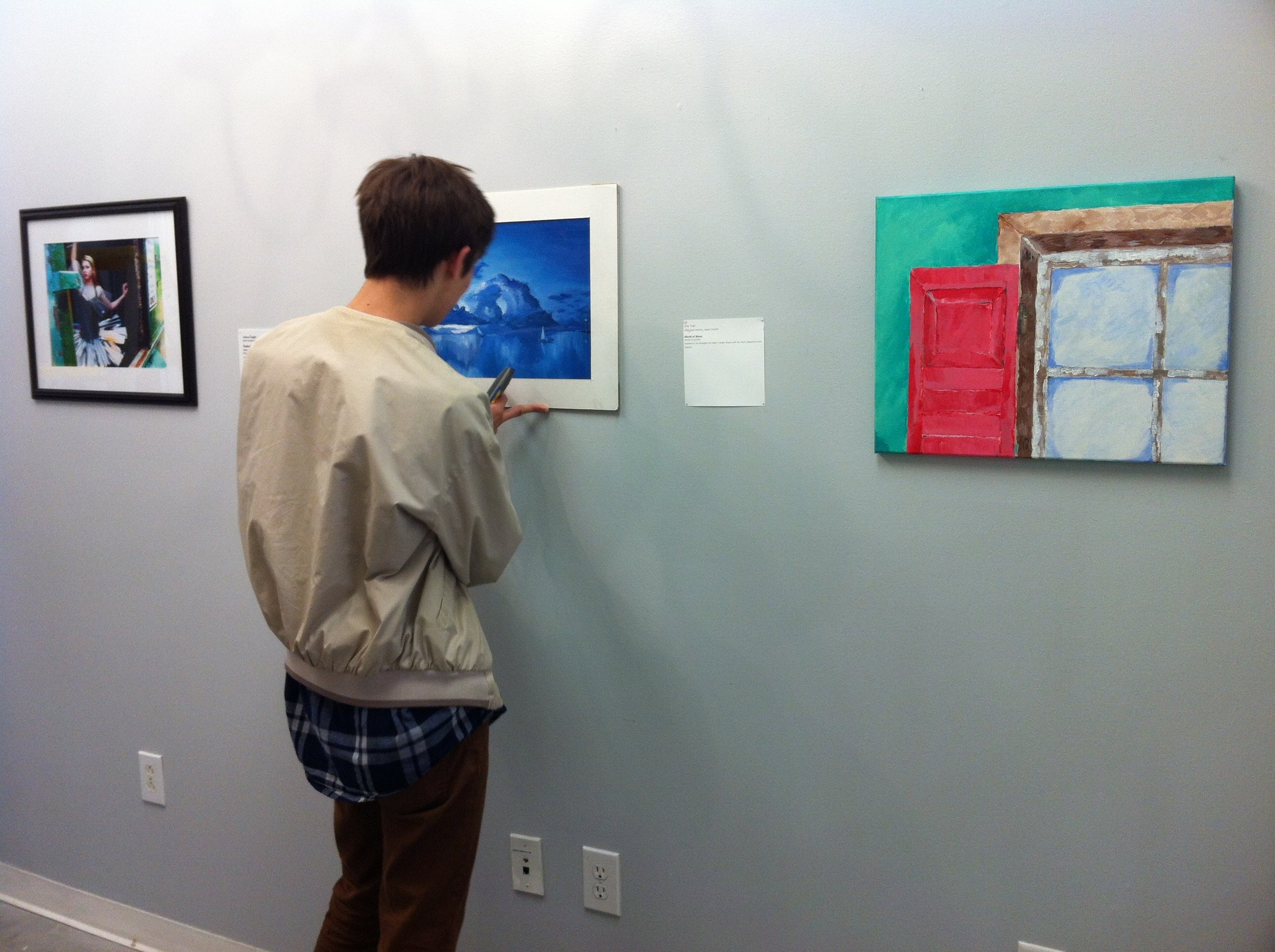 A Teen Arts Council member helps install the high school exhibition at a local art gallery.