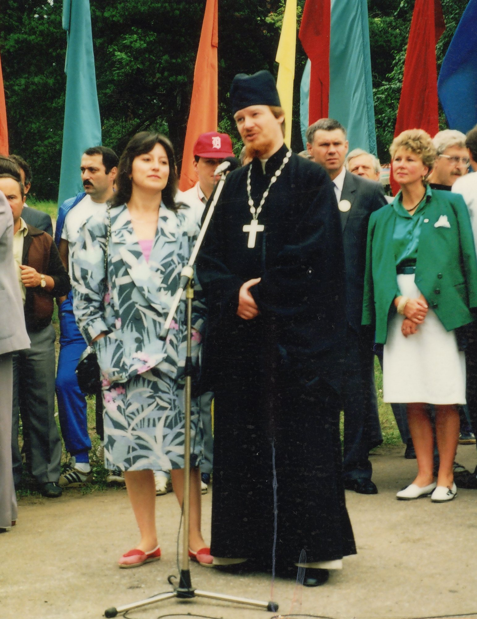 A Russian orthodox priest blesses the athletes with the translator by his side. The woman in green in the back is the mayor.