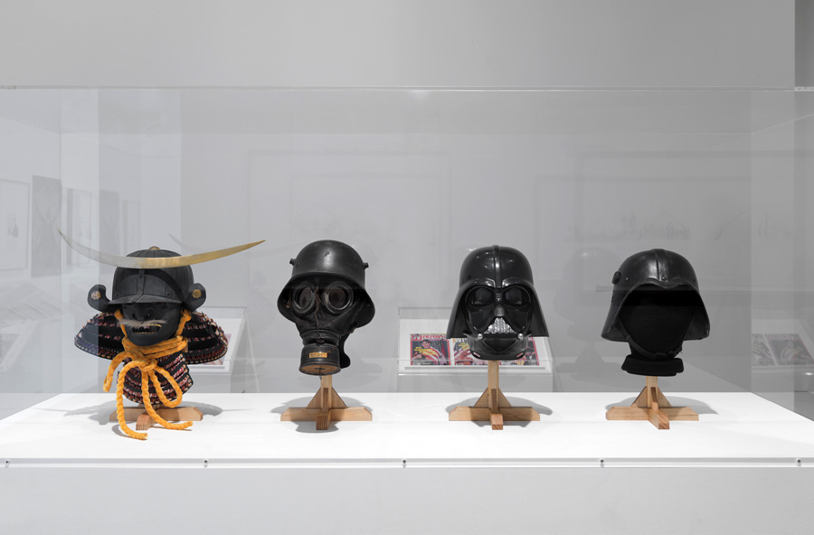 Next to these examples sit Darth Vader's helmet and one of the Iraqi Fedayeen Saddam helmets, thus conveying a timeline where examples from the battlefield inspire a Hollywood filmic mythology, which in turns inspires armor found on the battlefield.