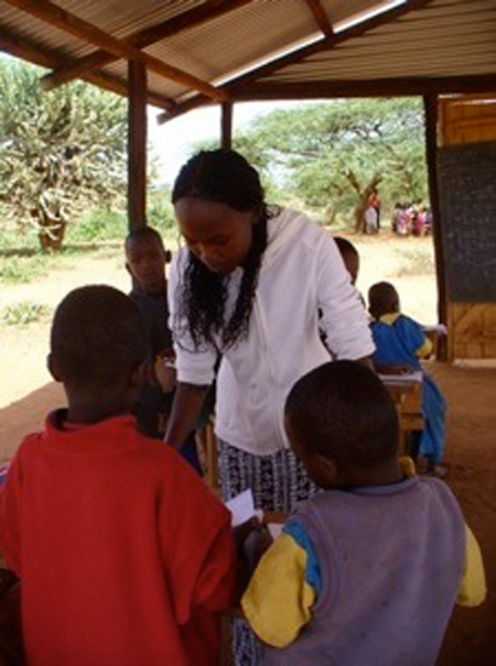 In the Isiolo district, teaching Intern Eunice instructs some young students in basic arithmetic.