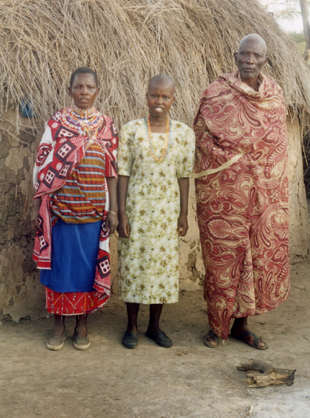 In front of one of the thatched mud huts of the family boma. Each wife has a separate hut.
