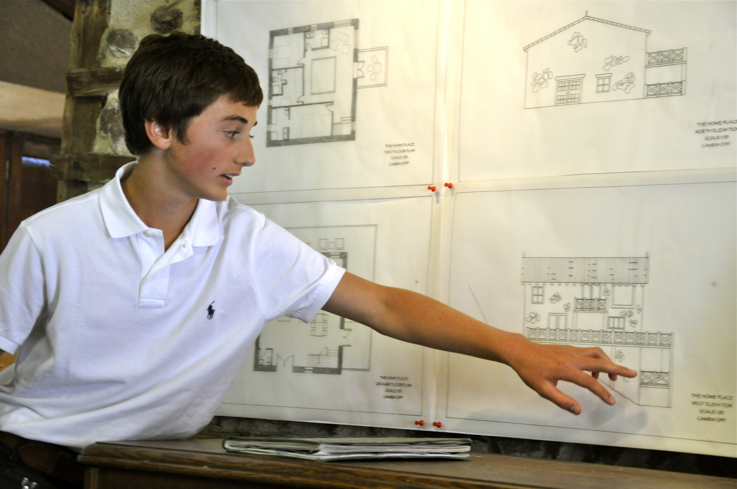 an architecture student presenting his technical drawings