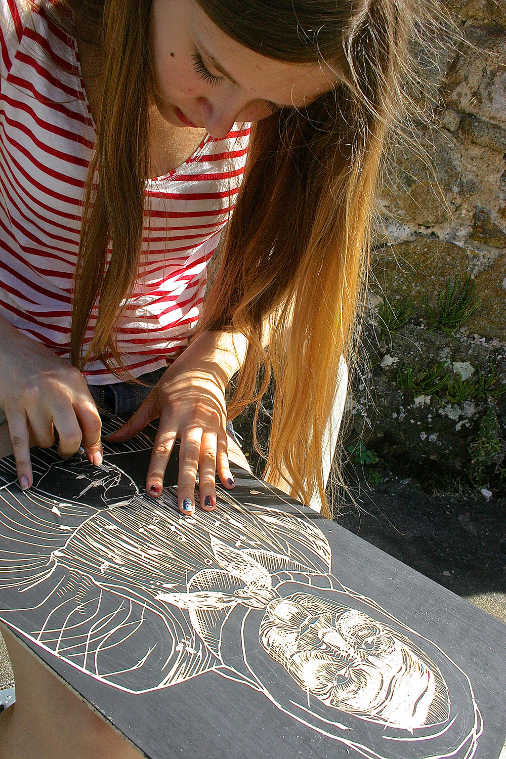 high school student working on a woodcut print at les tapies art programs