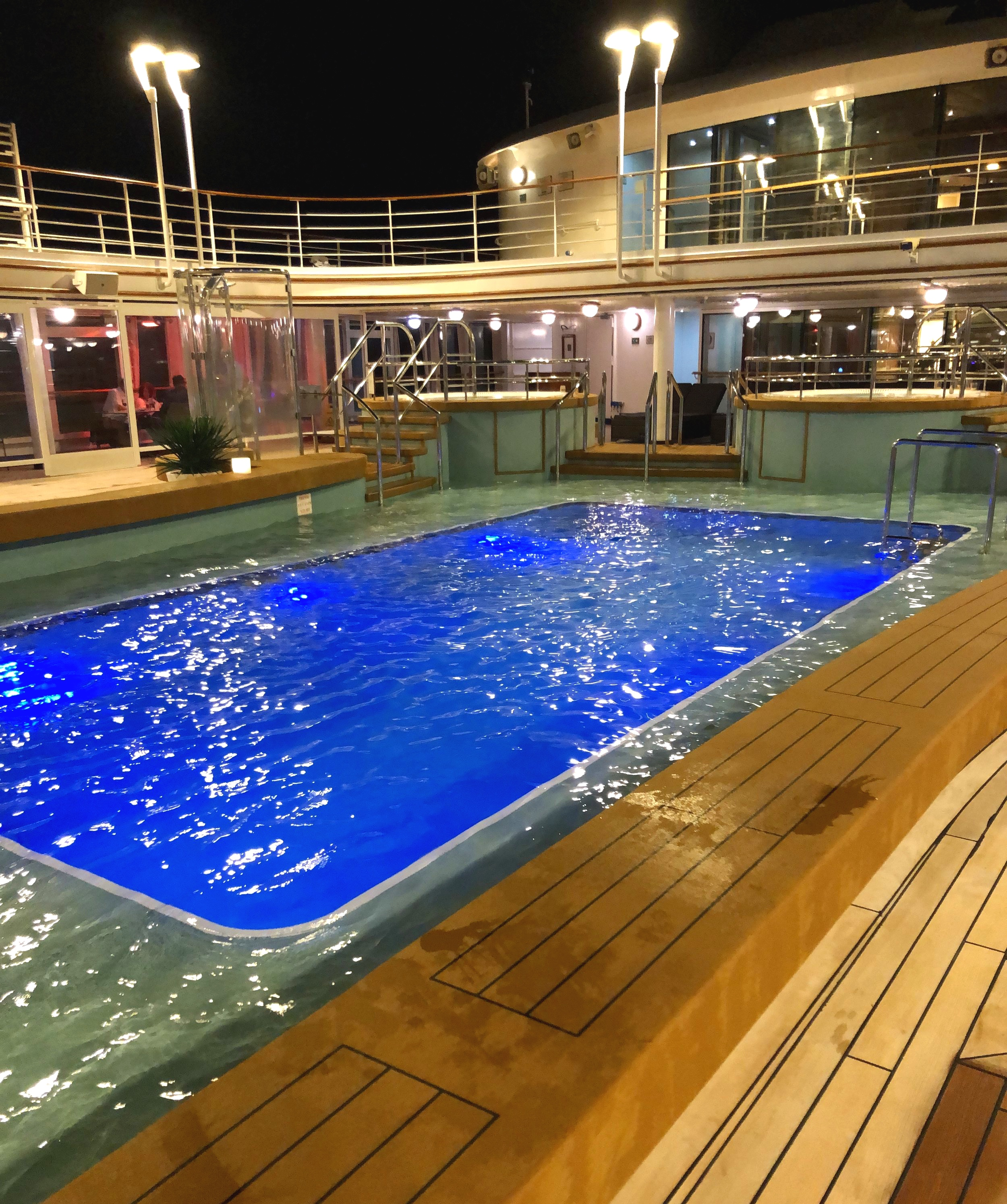 The beautifully lit pool deck at night.