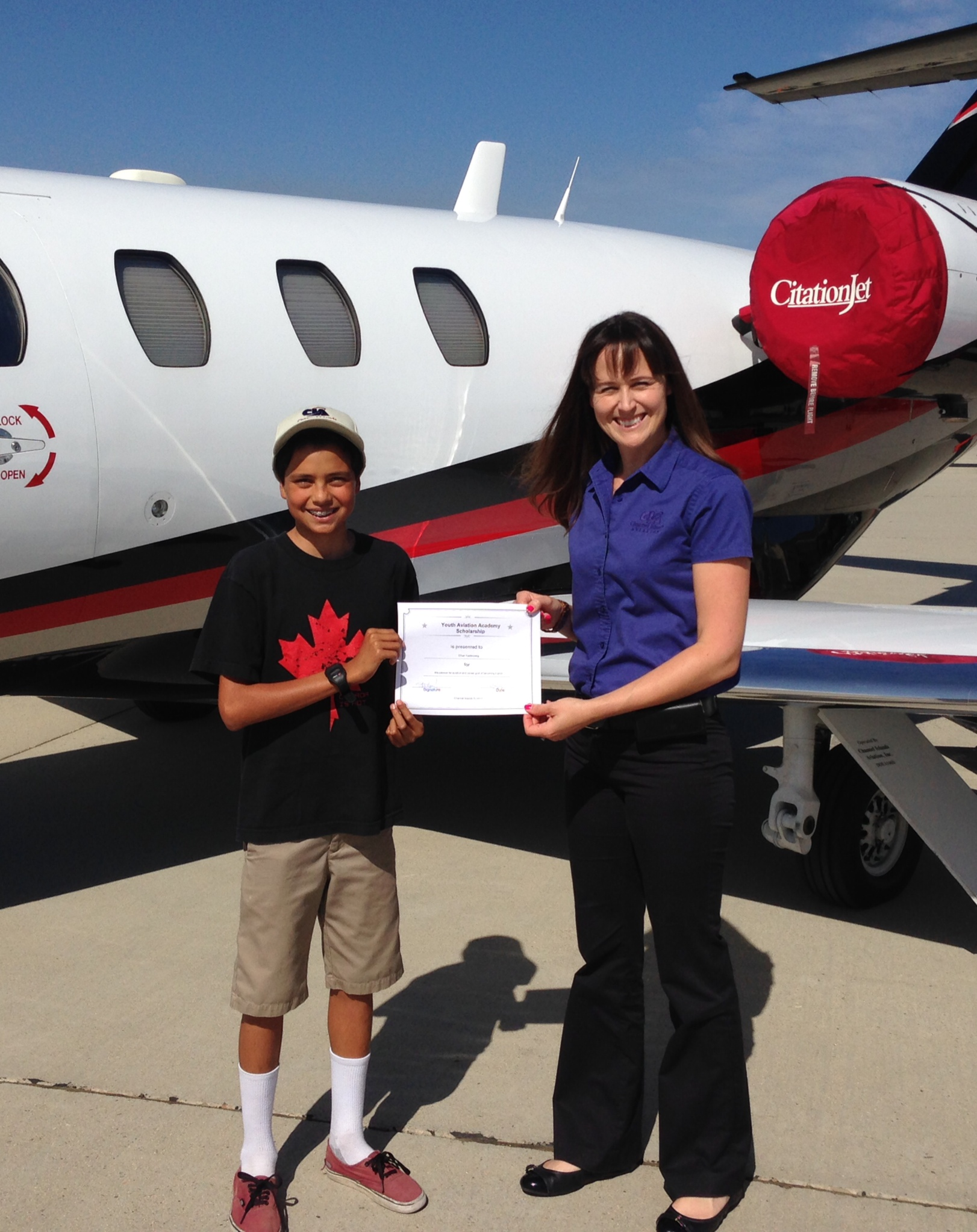 Ethan Kastenberg, 12, receives scholarship from Sarah Oberman Bartush, flight school manager.