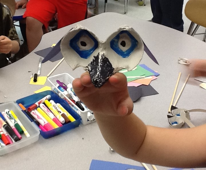 A student shows off their dog rod puppet in process.