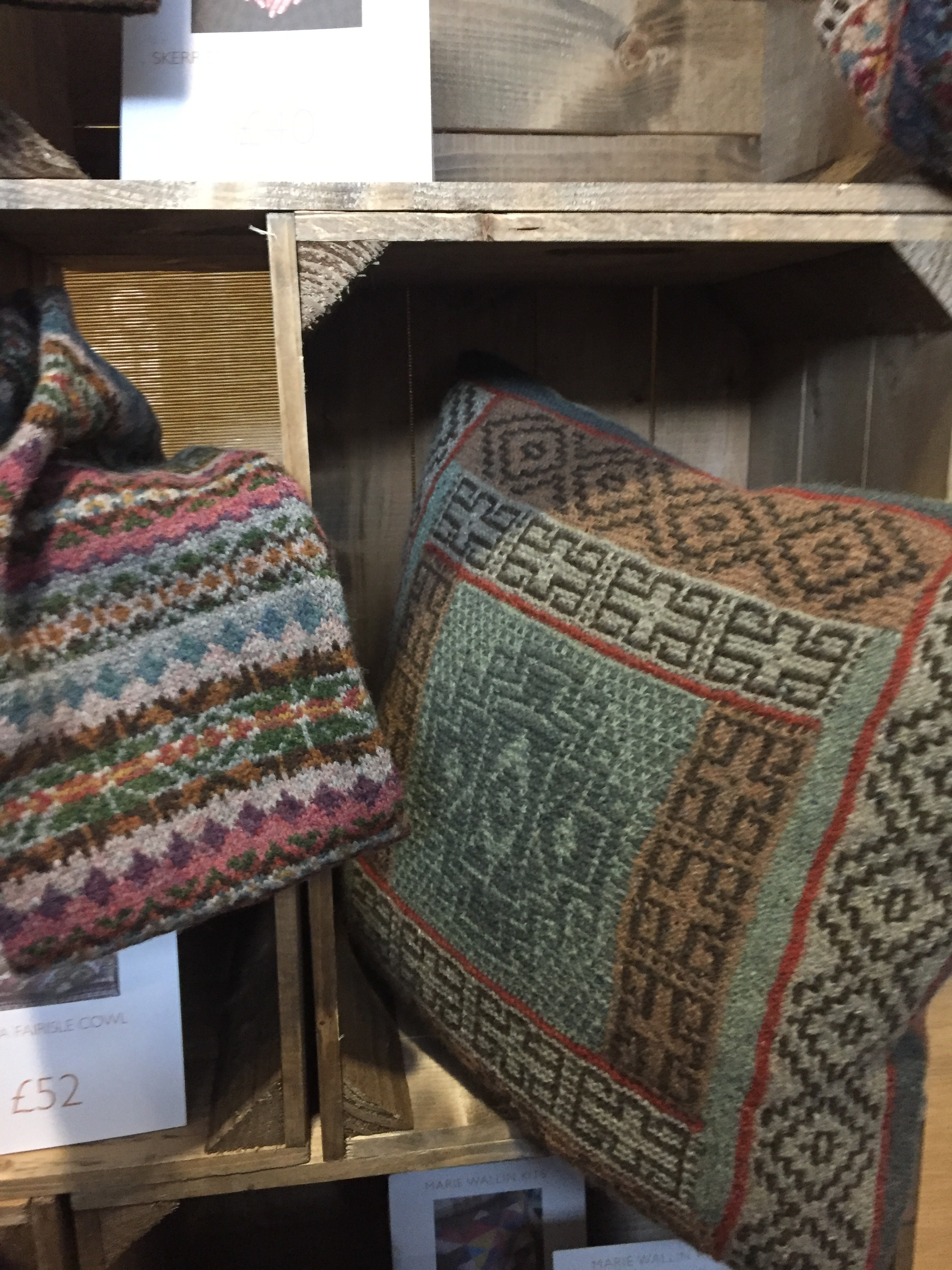Photo taken by Aleks Byrd of samples from Marie Wallin Designs' booth at Nottingham Yarn Expo showcasing home goods (pillows) and accessories (cowl) 2017.