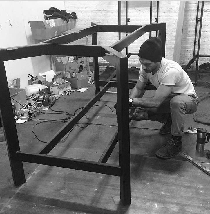 Jason Hernandez working on a blackened steel table base.