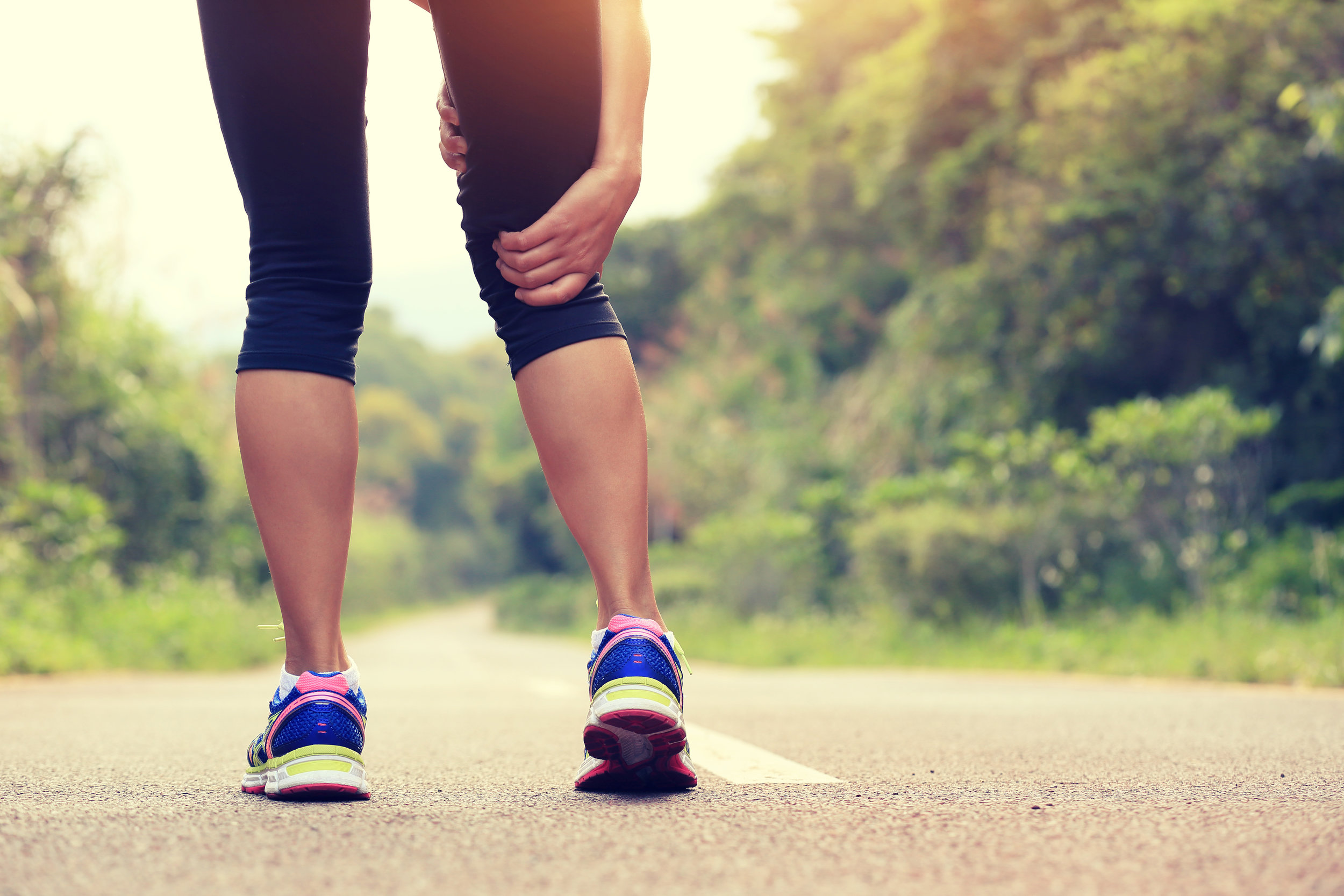 Woman runner hold her sports injured leg.jpg