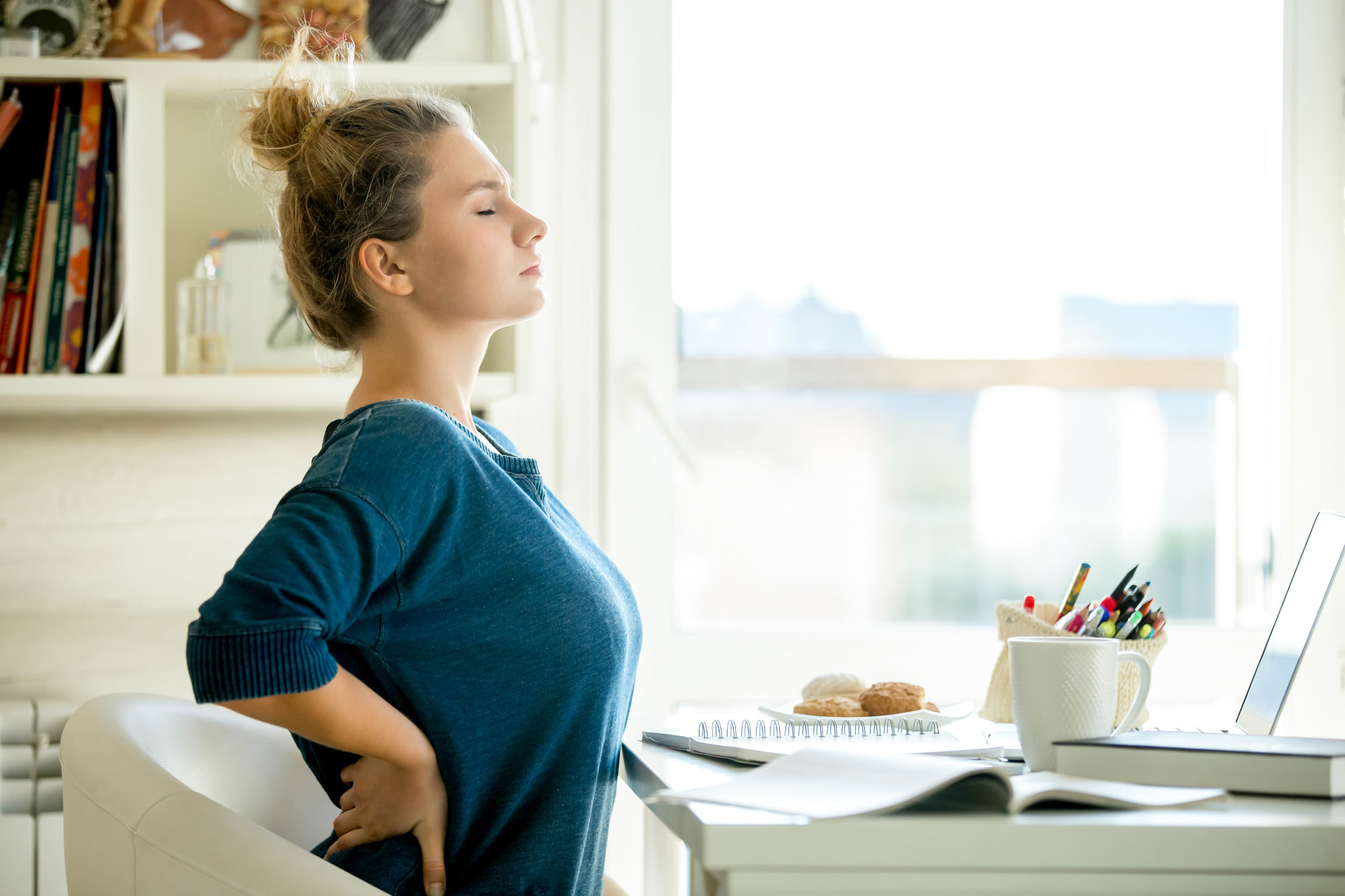 woman sitting at table with hands on back in pain.jpg