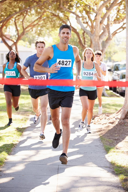 Group of runners with male runner winning race in sunshine.jpg