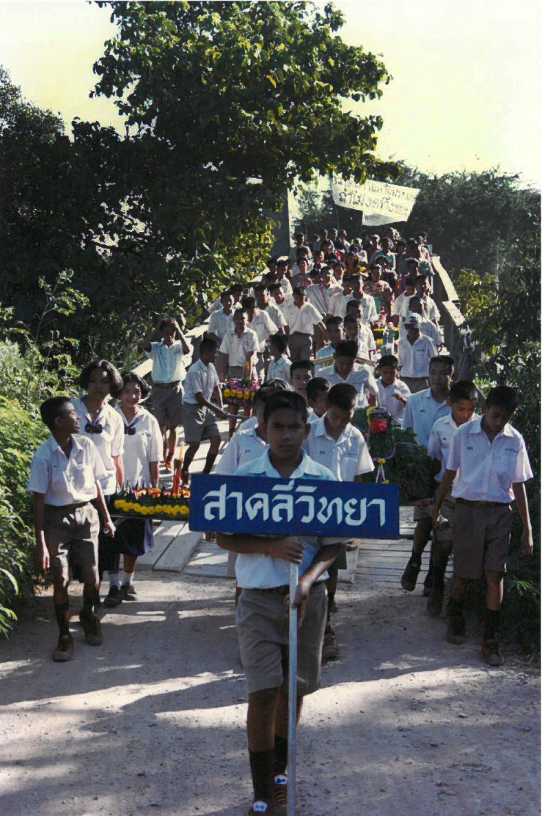 My students walking over the bridge in our village during a ceremony. The sign says Sa Klee Wittaya, the name of their school.