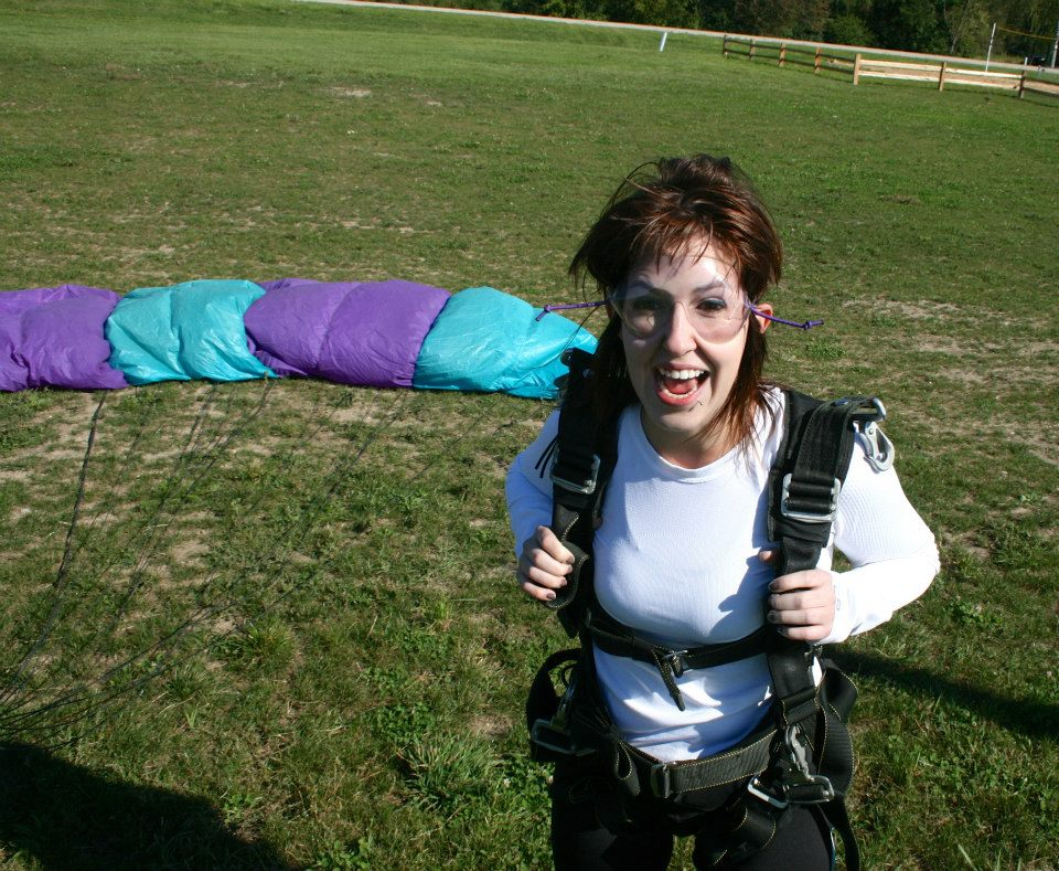 (Image Description: I'm standing in a field with a parachute backpack on and a parachute behind me after landing from skydiving. I have a really goofy, excited look on my face and my hair is wild.)