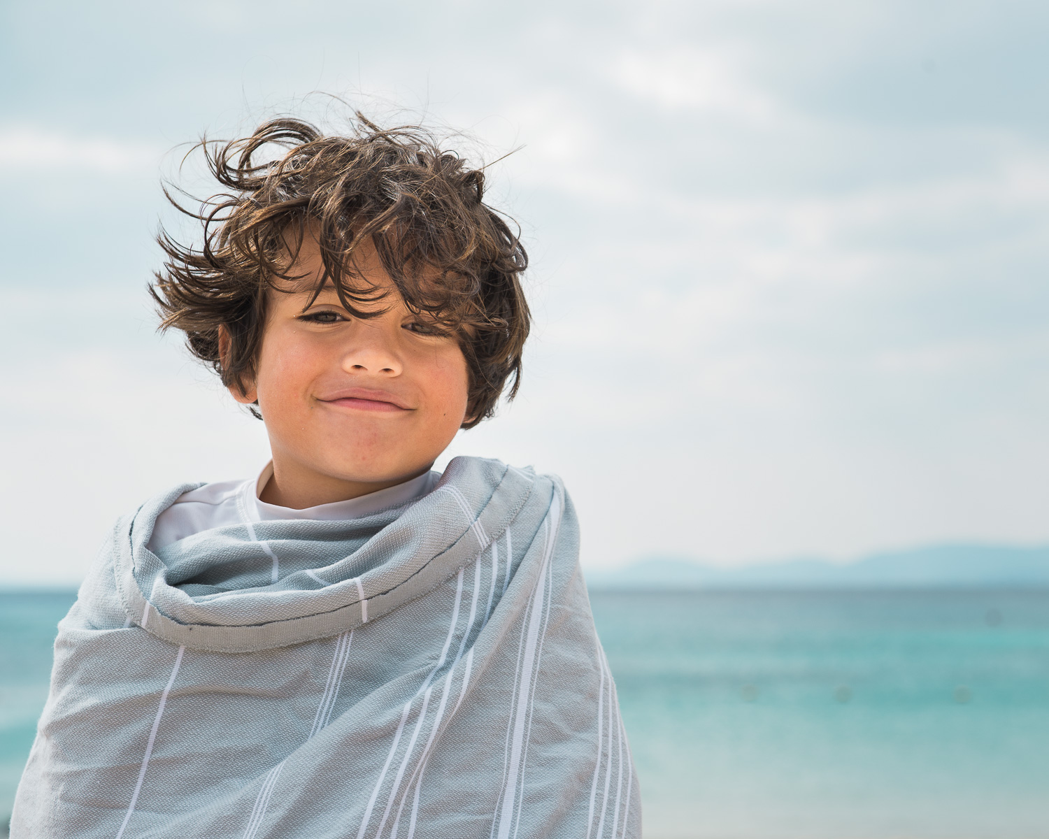 boy wrapped up by the ocean
