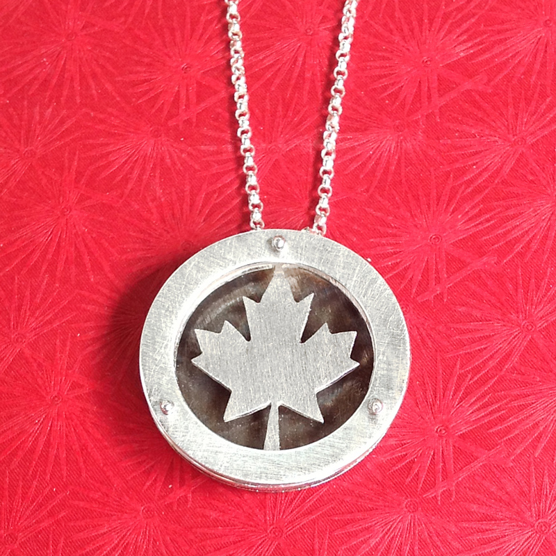 Large circle shadowbox necklace with Canadian maple leaf.