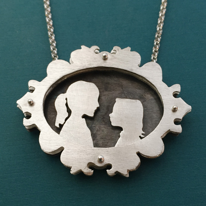 Ornate shadowbox necklace with silhouette of children.