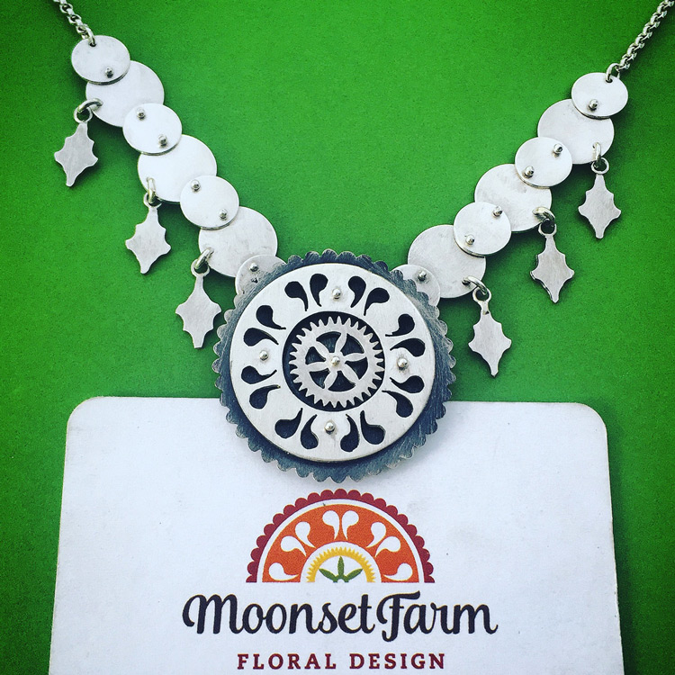 Necklace with decorative chain and center design to match business card logo. Center of the design spins.