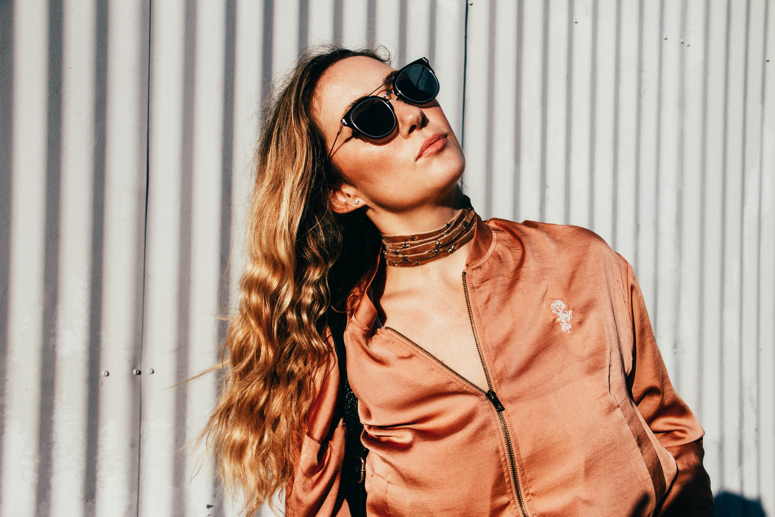 "Wearing Urban Outfitters ""Cleo"" peach satin bomber, $79, find it  here . Ettika x Free People Choker  here  ."