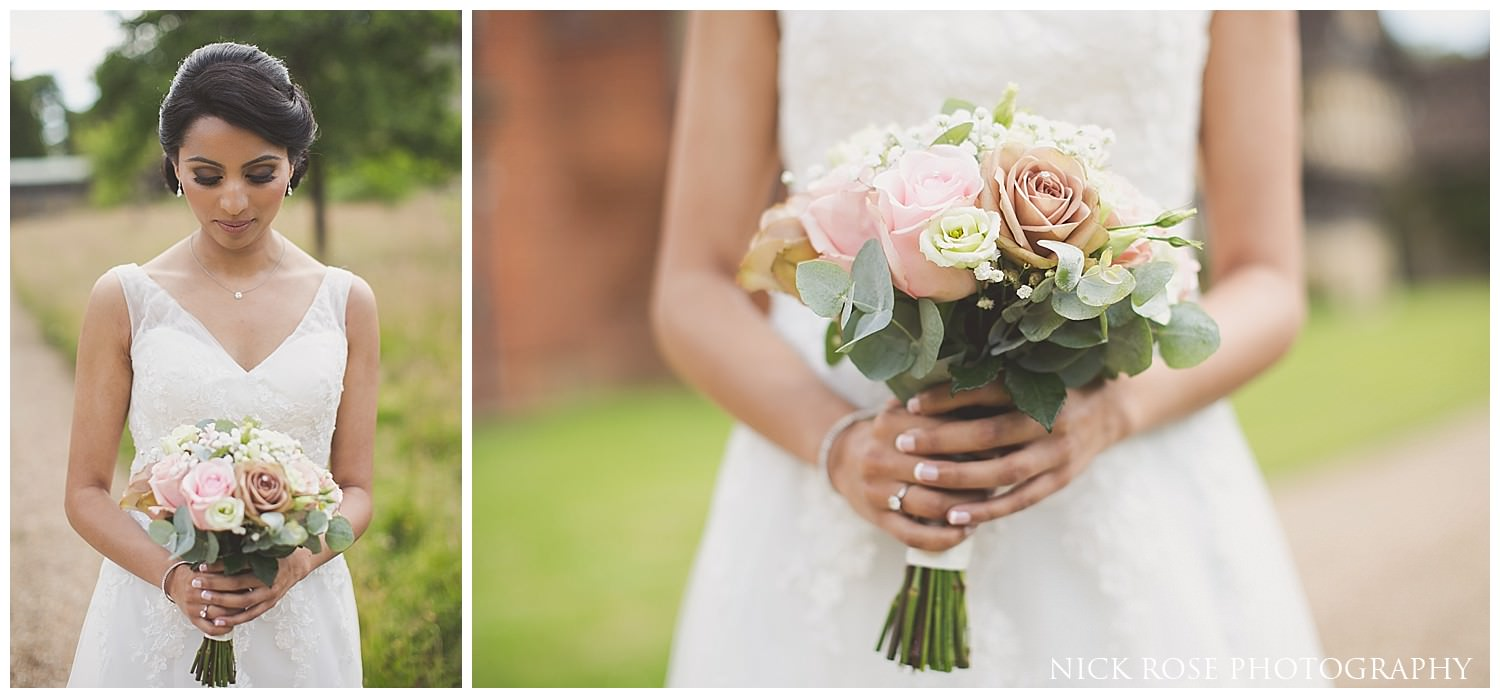 Indian bride in a white dress holding a boquet of flowers before a wedding at Hever Castle