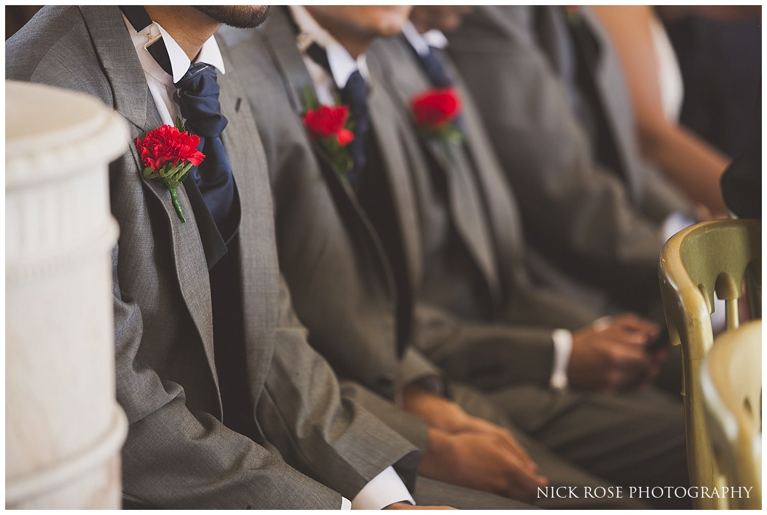 Wedding ushers in Hever Castle with red flowers