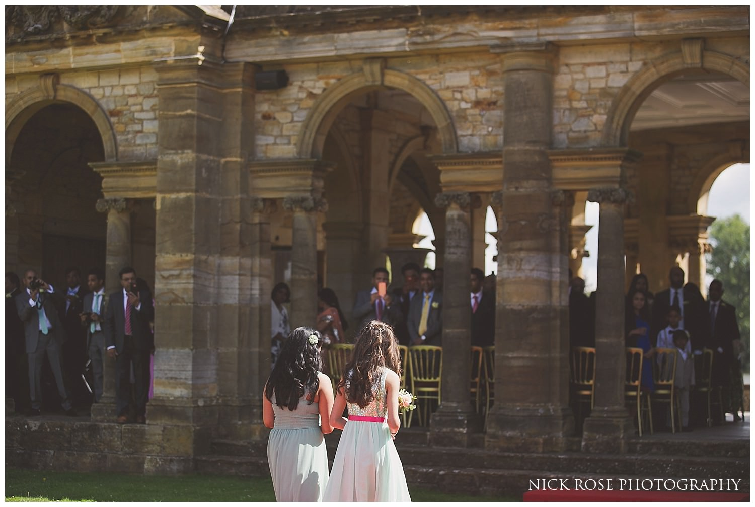 Bridesmaids walking up the aisle for an outdoor kent wedding at Hever