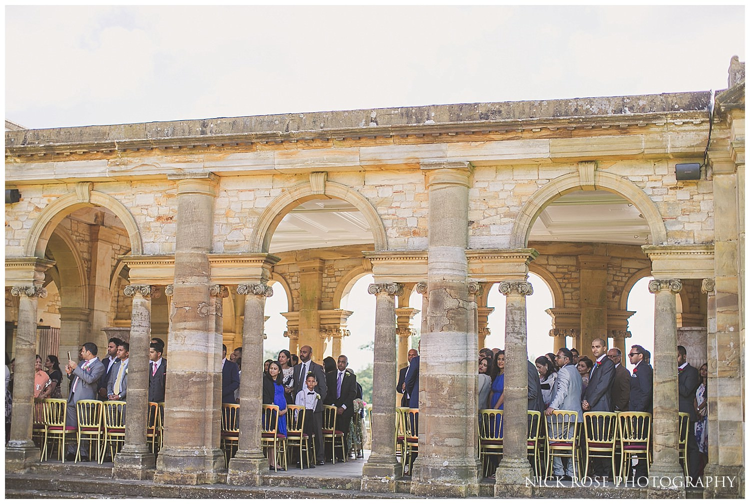 Guests watching bride walk up the red carpet in the Hever Castle Italian gardens in Kent