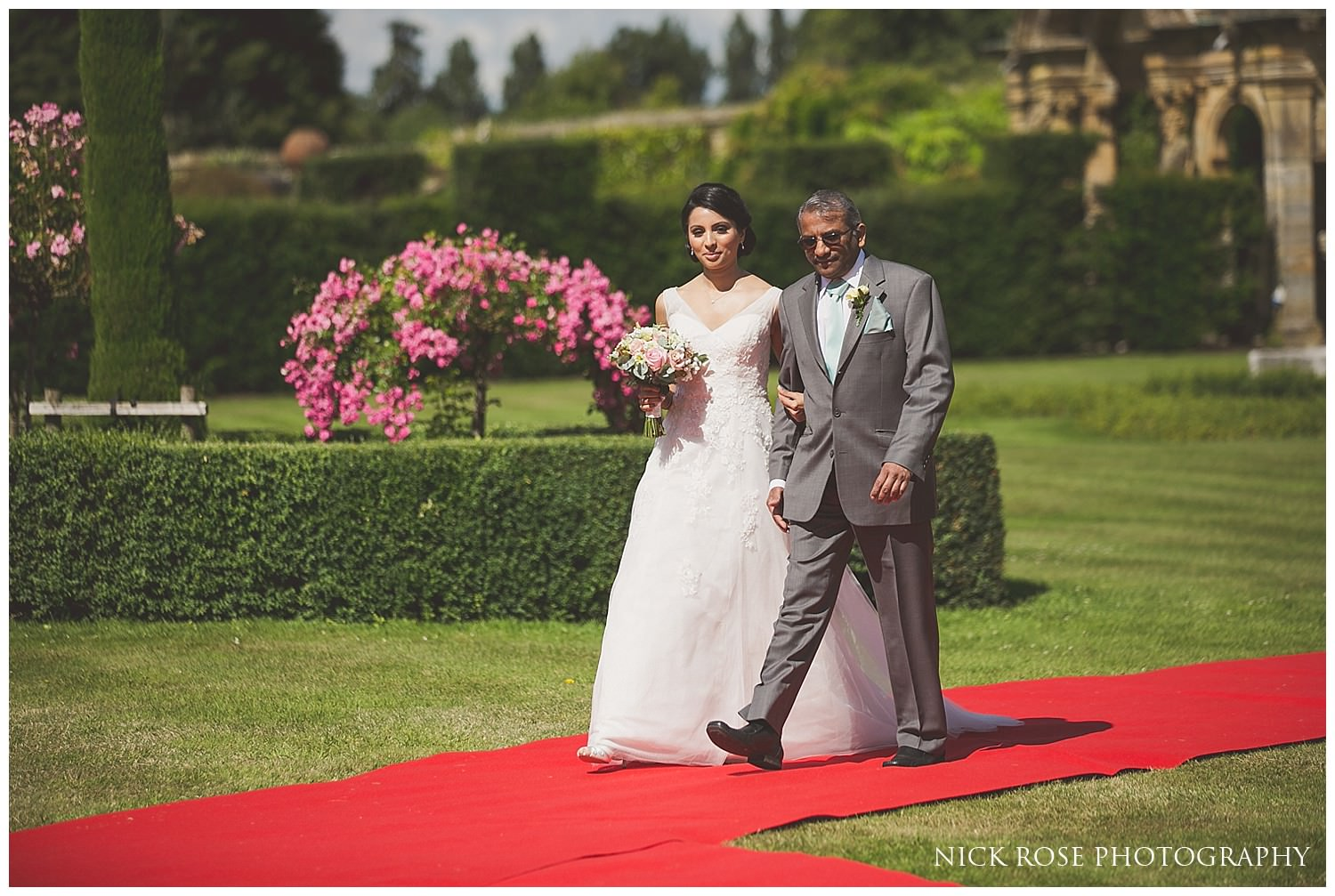 Father of the bride walking daughter up the red carpet aisle at hever castle