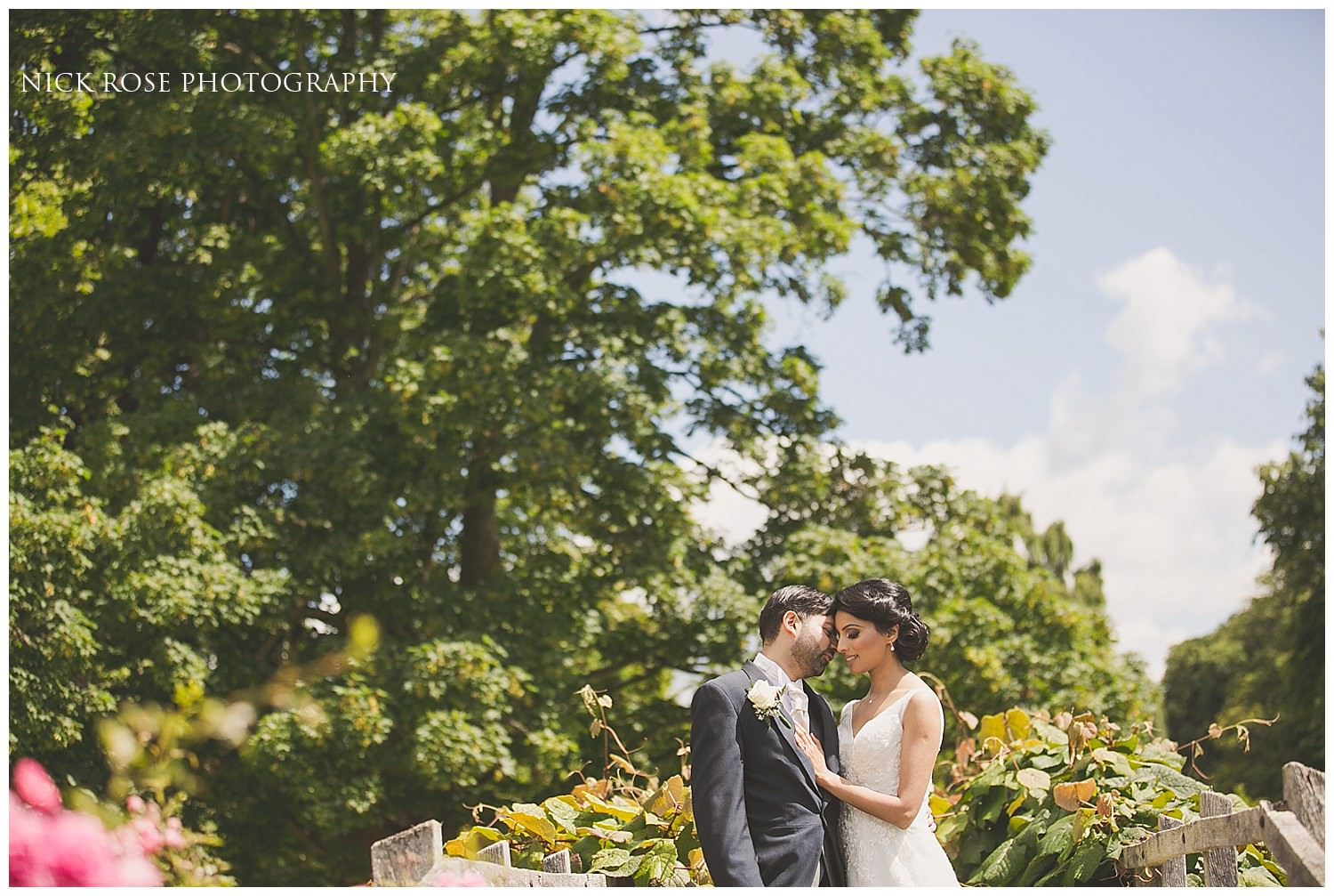 Bride and groom kissing in the Hever Castle gardens in Kent
