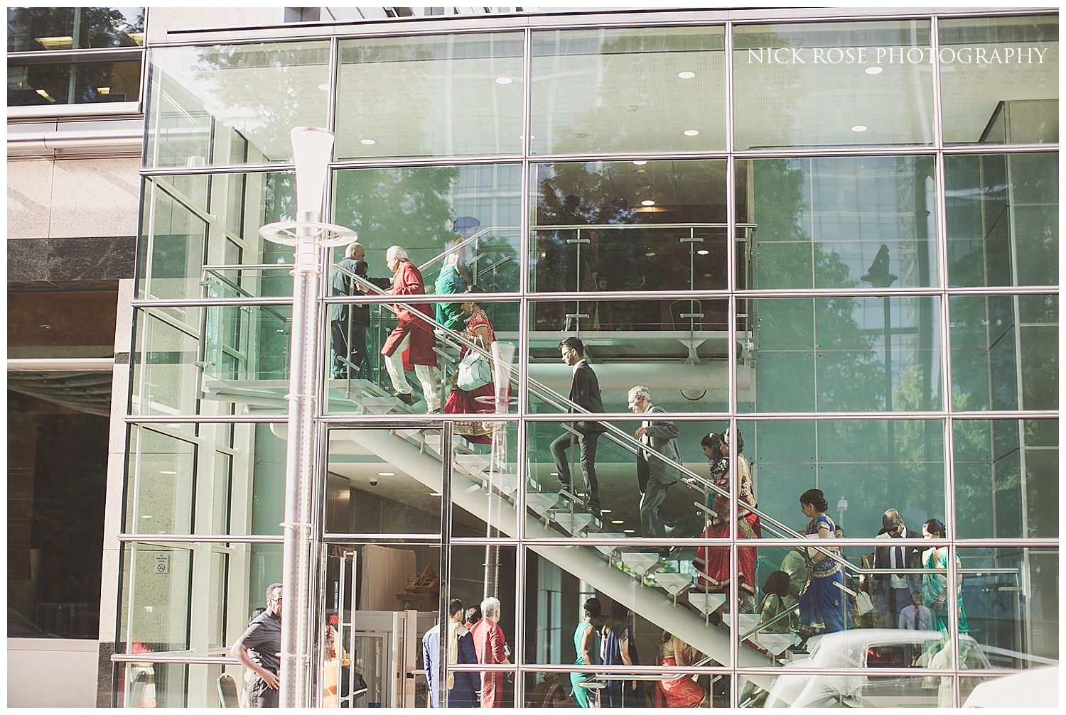 Guests walking up the glass staircase at East Wintergarden in Canary Wharf London before an Indian wedding