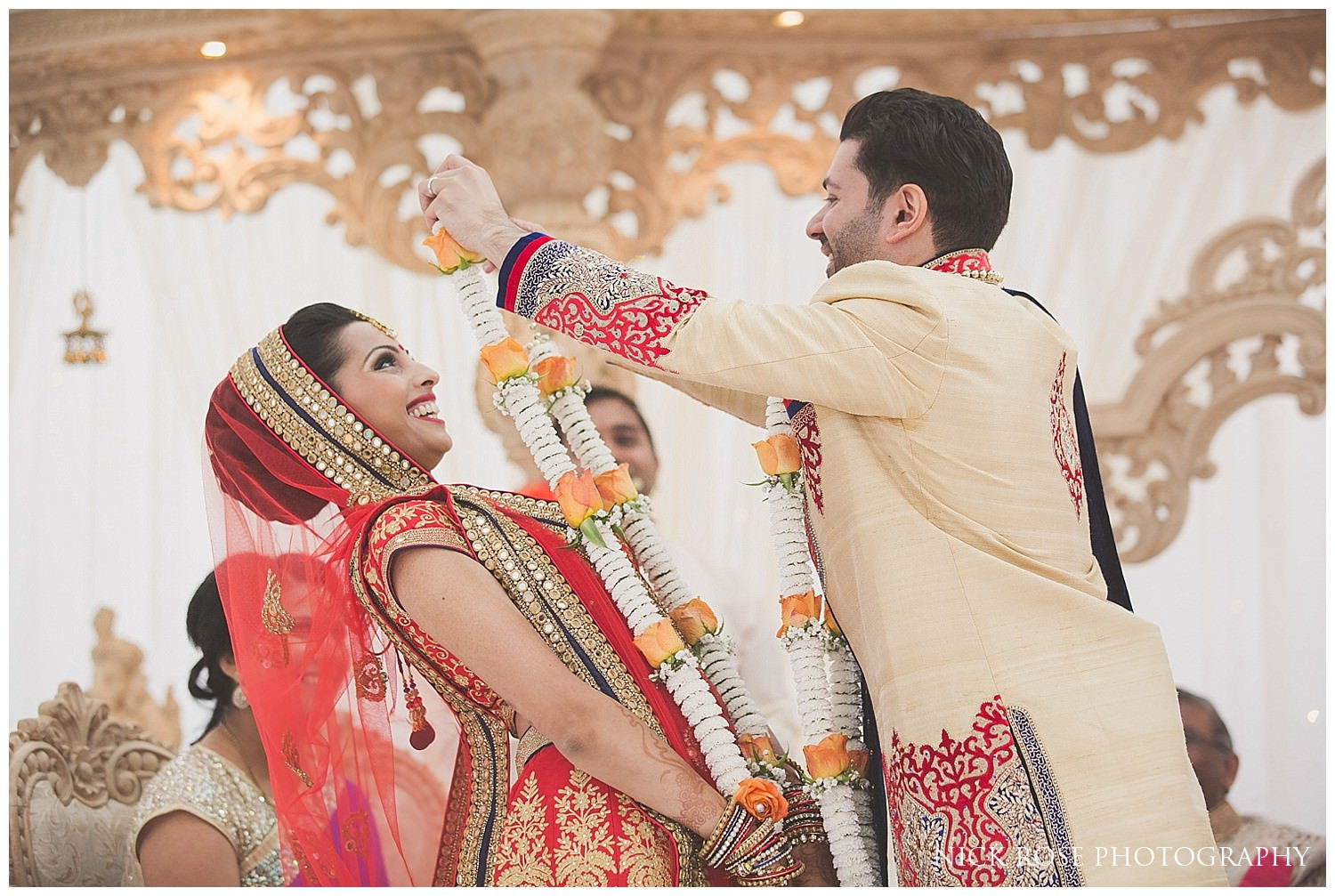Bride and groom exchanging garlands during an Indian East Wintergarden Hindu wedding in Canary Wharf London