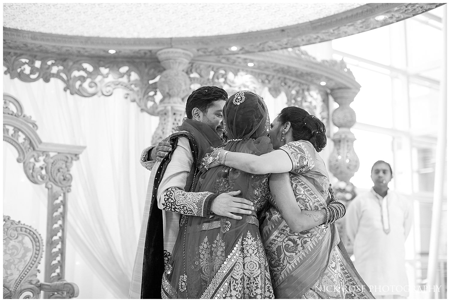 Family hugging during an Asian Hindu wedding in the East Wintergarden at Canary Wharf London