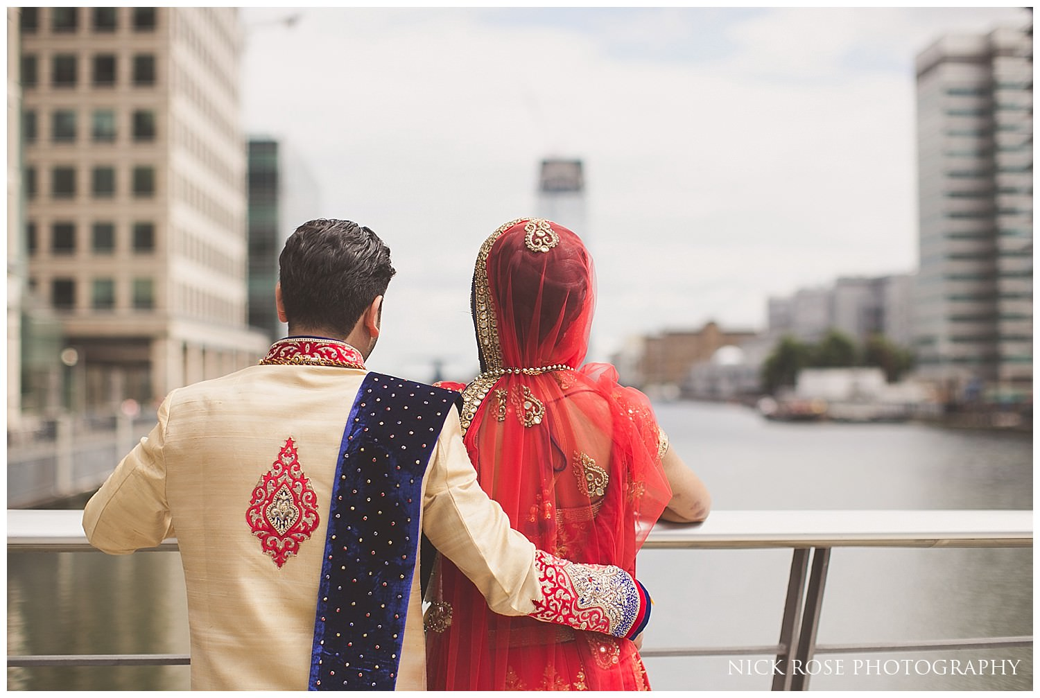 Indian bride and groom looking over the water at Canary Wharf in London