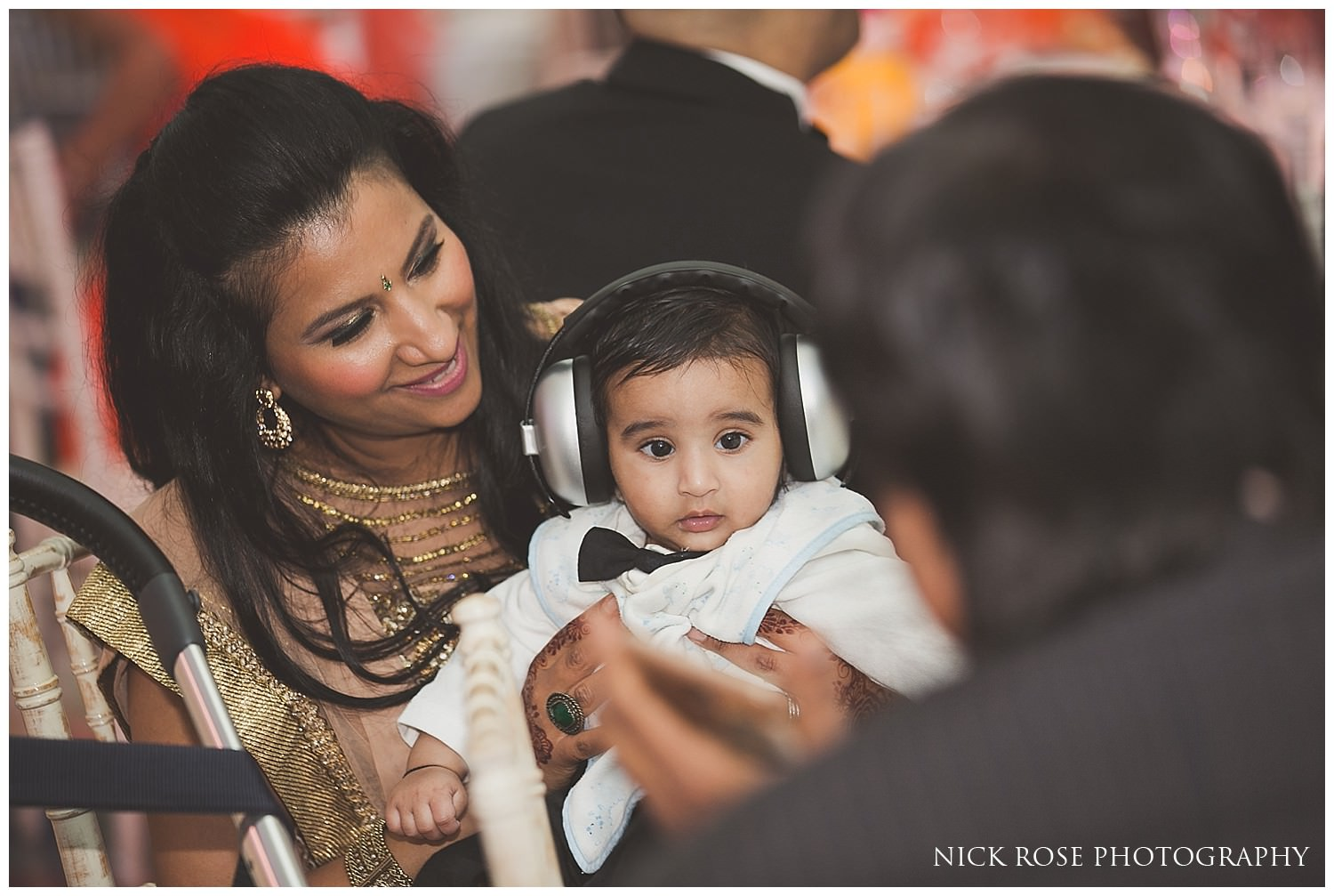 Baby with ear defenders for an Asian wedding in London