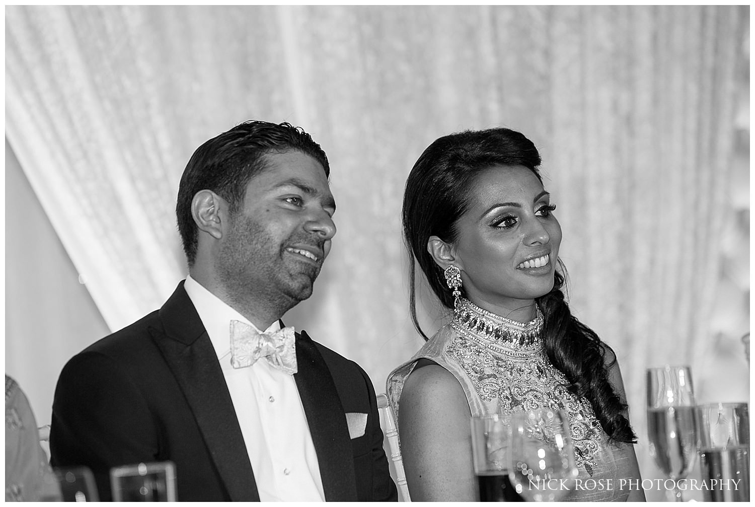 Couple listening to speeches during an Indian wedding reception in Canary Wharf London