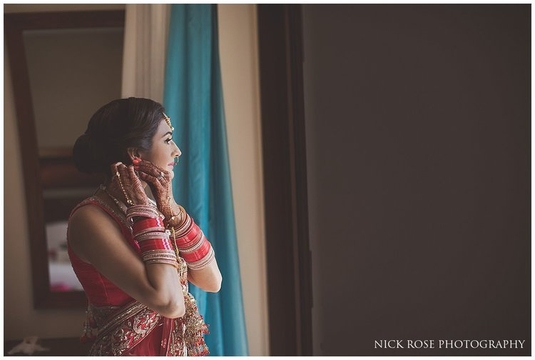 Asian bride putting on earrings before her destination Hindu wedding in Dubai