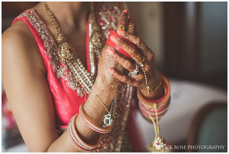 Indian bride putting on bracelet and bangles for a Hindu wedding at the Sofitel Palm Dubai