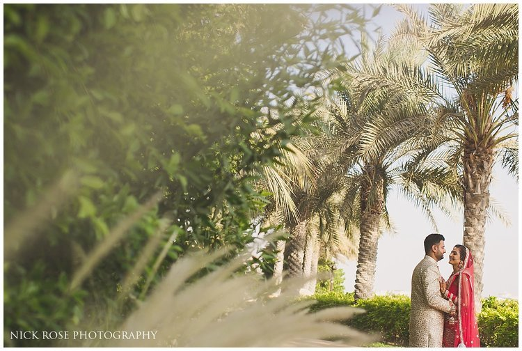 Bride and groom under palm trees in Dubai for a destination Hindu wedding at the Sofitel Palm Dubai